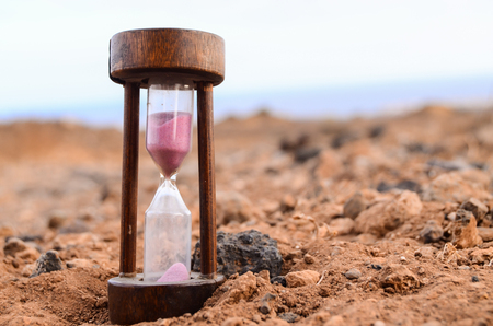 hourglass: Time Concept Hourglass on the Rock Desert