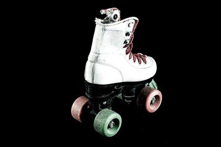 consumed: Used Vintage Consumed Roller Skate on a Black Background