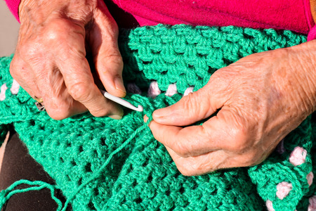 needle: Close-up image of an old woman with knitting needles and wool