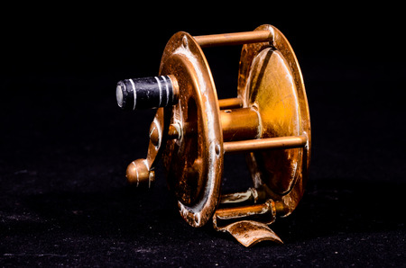 fishing reel: One Vintage Old Metal Fishing Reel on a Black Background