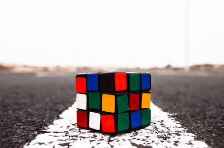 Rubiks Cube Solved on the Asphalt Road Stock Photo