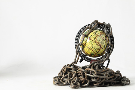 slavery: Earth globe close in chain and padlock Stock Photo