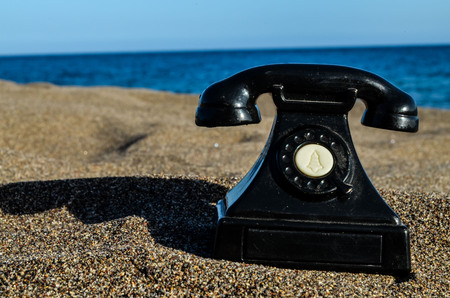 oversea: Photo Picture of an Old Phone on the Sand Beach
