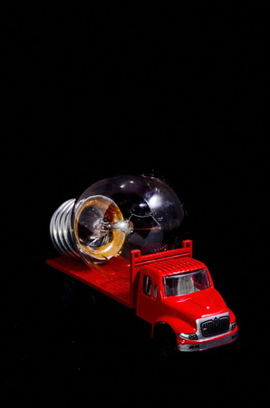 red truck: Electric Power Concept Red Truck and Light Bulb on a Black Background Stock Photo