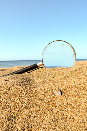 turistic: Photo Picture of a Loupe Magnify Glass on the Sand Beach Stock Photo