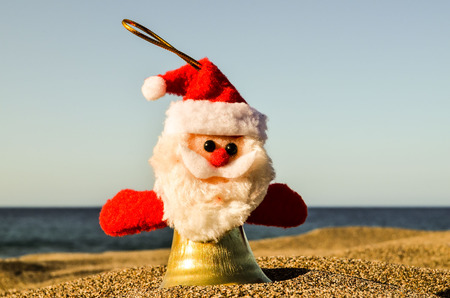 Photo Picture of Santa Claus Toy on the Sand Beach Stock Photo