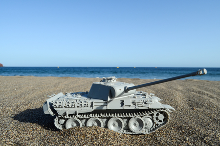 War Concept Gray Tank Model on the Beach Stock Photo