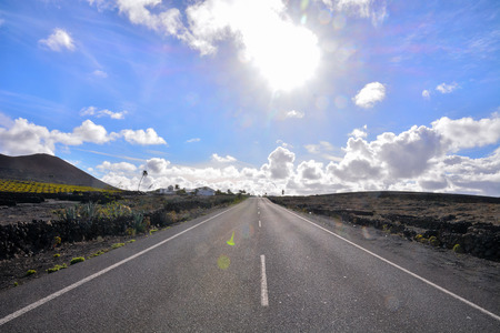 desert road: Spanish View Desert Road Landscape in Lanzarote Tropical Volcanic Canary Islands Spain Stock Photo