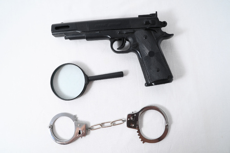 Criminality Concept Gun and Handcuffs on a White Background