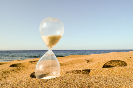 Photo Picture of Hourglass Clock on the Sand Beach Stock Photo