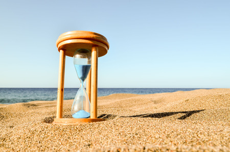Photo Picture of Hourglass Clock on the Sand Beach Stok Fotoğraf - 70527402