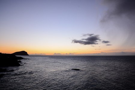 Photo Picture of The Sun Setting in the Sea Stock Photo