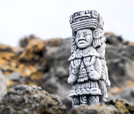 Antiguo maya estatua en las rocas cerca del océano