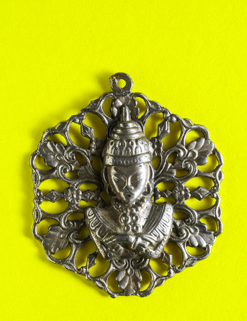 Silver Buddha Pendant Jewel over a Colored Background