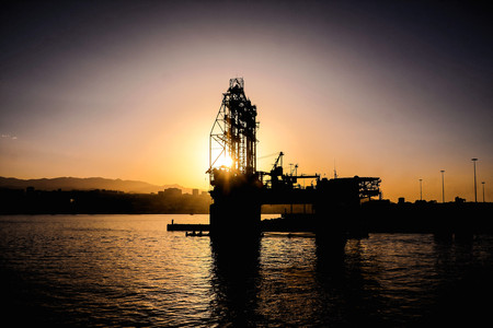Silhouette of an offshore petrol drilling rig and supply vessel at sunset Stock Photo