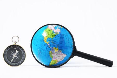 オリエンテーションコンセプト地球、白い背景にガラスとコンパスを拡大