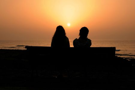 Two Silhouetted Girls at Sunset near the Atlantic Ocean Stock Photo