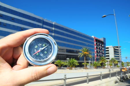 Orientation Concept a Male Hand Holding a Metal Compass in a City Stock Photo