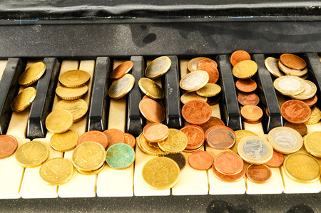Photo picture close-up of piano keys keyboard and coin money