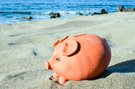 Photo Picture of Piggy Bank on the Sand Beach Stock Photo