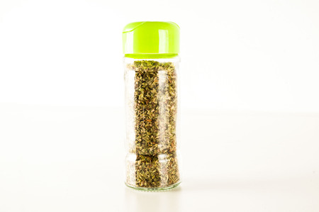 Bottle of dried oregano leaves isolated on white background Stock Photo