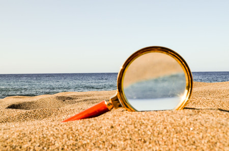 Photo Picture of a Loupe Magnify Glass on the Sand Beach Stock Photo
