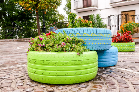 Old tires that are painted in assorted colors and used for a flower planter