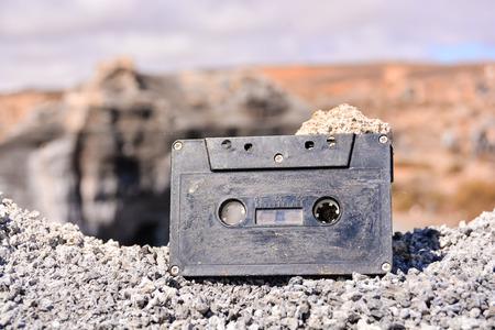 Konzeptionelles Fotobild eines Musikbandkassettenobjekts in der trockenen Wüste Standard-Bild