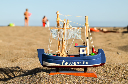Photo Picture of a Toy Boat on the Sand Beach