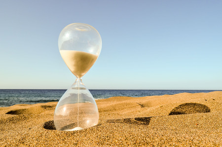 Photo Picture of Hourglass Clock on the Sand Beach 免版税图像