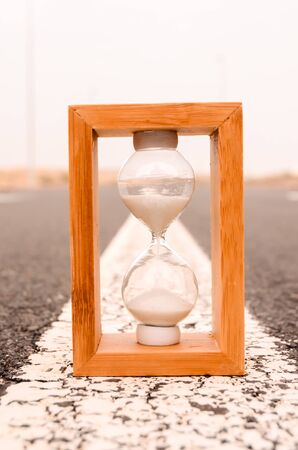 Time Concept Alarm Hourglass on the Asphalt Street Stock Photo