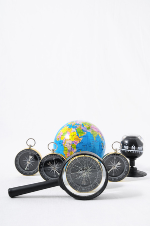 Orientation Concept Earth,Magnify Glass and Compass on a White Background