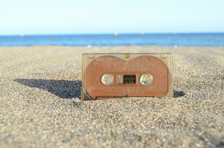 Ancient Retro Musicassette on the Sand near the Water Banque d'images