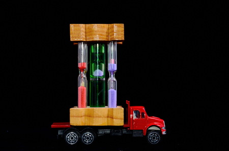 Time Transportation Concept Hourglass Watch on a Red Toy Truck over Black Background Banque d'images