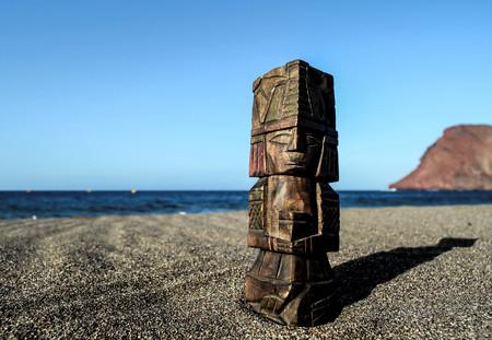Estatua maya antigua en la playa de arena cerca del océano