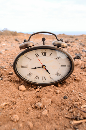 Classic Analog Clock In The Sand On The Rock Desert Imagens