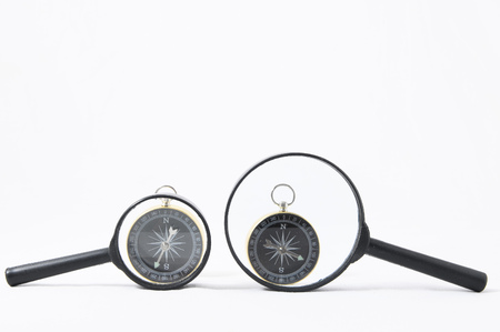 Orientation Concept Magnify Glass and Compass on a White Background Stock Photo - 121499709
