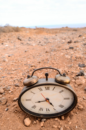 Classic Analog Clock In The Sand On The Rock Desert Stock Photo