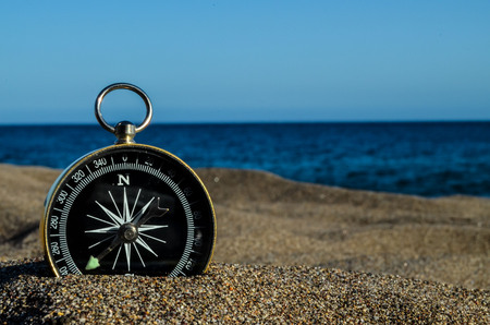 Fotobeeld van een kompas op het zandstrand