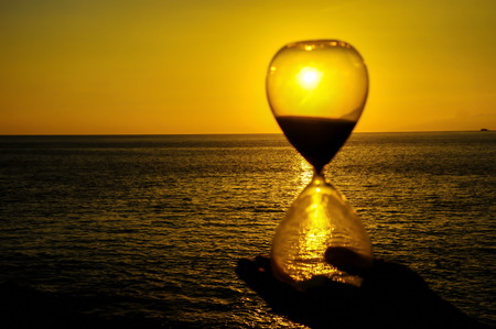 Time Concept Hourglass and Sun Setting on the Atlantic Ocean Standard-Bild - 122060175