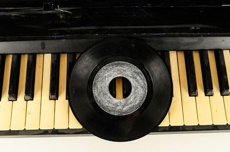Photo picture close-up of piano keys keyboard and vinyl disk record 写真素材