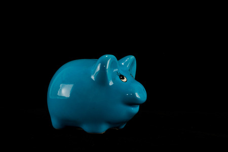 Blue piggy bank or money box isolated on a black studio background 写真素材 - 124616420