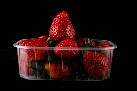 fresh strawberries in box isolated on black background