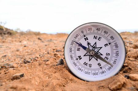 Orientation Concept Metal Compass on a Rock in the Desert Foto de archivo - 124978007