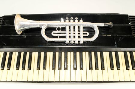 Photo picture close-up of piano keys keyboard and trumpet