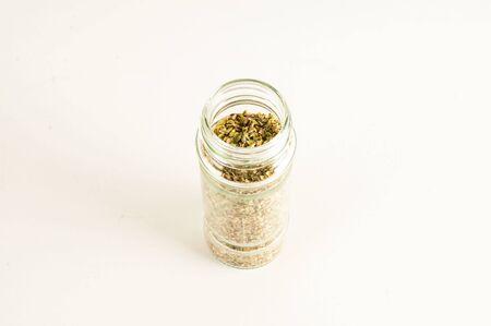 Bottle of dried oregano leaves isolated on white background