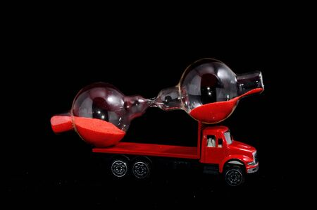 Time Transportation Concept Hourglass Watch on a Red Toy Truck over Black Background Stock Photo