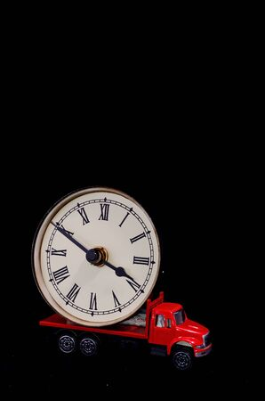 Time Transportation Concept Clock Watch on a Red Toy Truck over Black Background 版權商用圖片