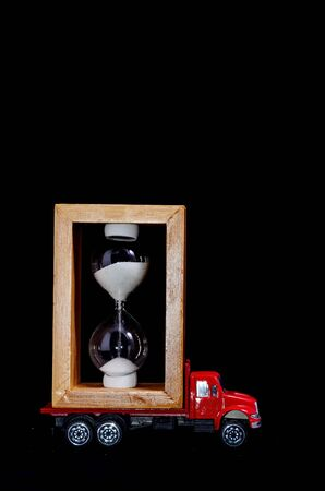 Time Transportation Concept Hourglass Watch on a Red Toy Truck over Black Background 版權商用圖片