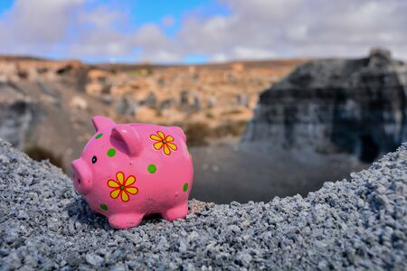 Conceptual Photo Picture of a Piggy Bank Object in the Dry Desert